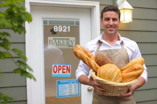 Happy Entrepreneur Holding Bread Basket